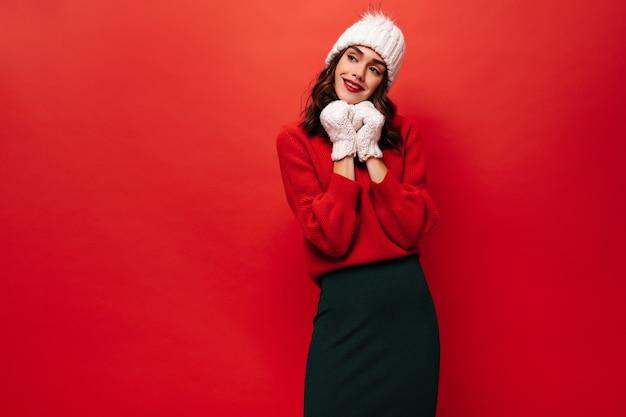 Retrato de dama encantadora en falda negra, suéter brillante, gorro de punto y mitones sonriendo y posando en la pared roja