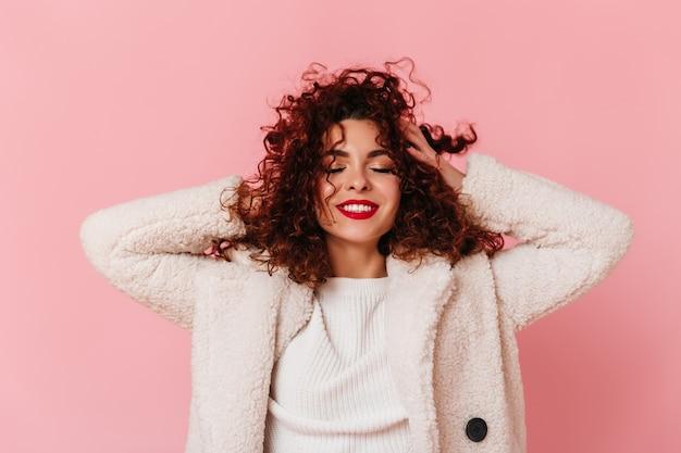 Retrato de dama encantadora con lápiz labial rojo y sonrisa blanca como la nieve vestida con un abrigo ecológico brillante y tocando su cabello rizado en el espacio rosa.