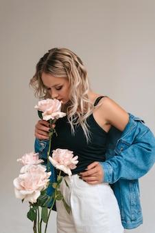 Retrato de dama encantadora mirando flores y oliéndolas.