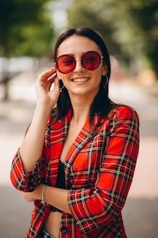 Retrato de dama joven en chaqueta roja y gafas de sol rojas
