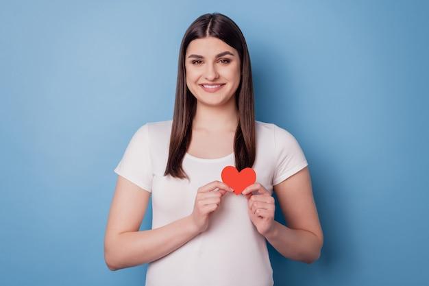 Retrato de dama linda cariñosa mantenga poco papel tarjeta roja en forma de corazón sobre fondo azul.