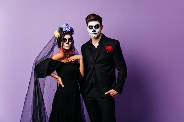Retrato de dama sorprendida en imagen de novia para halloween y su novio en traje clásico con cara pintada en forma de calavera.