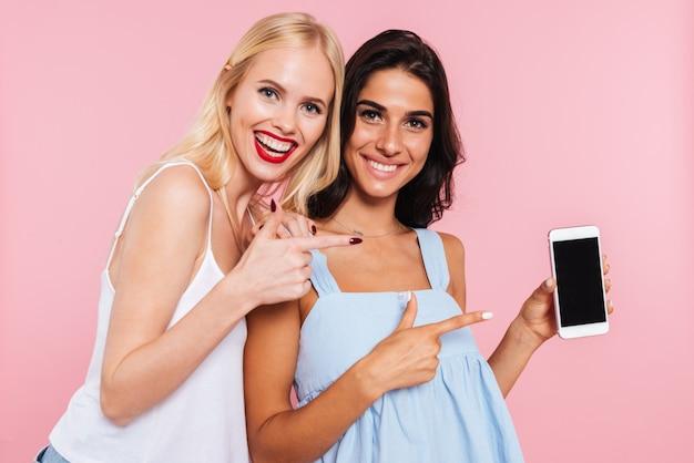 Retrato de damas alegres que muestra la pantalla en blanco del teléfono inteligente aislado