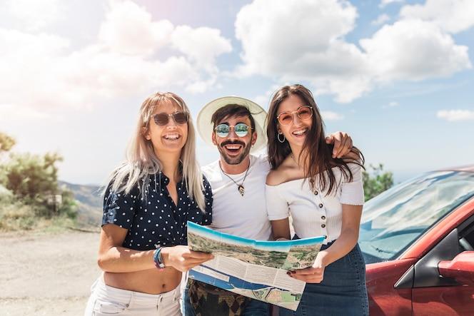Retrato de amigos de pie cerca del mapa de la celebración del coche