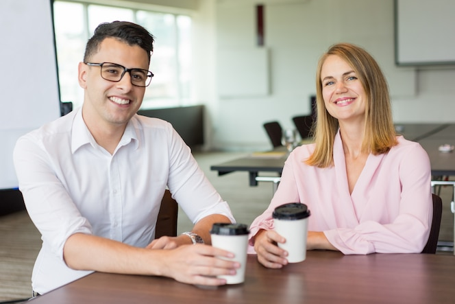 Retrato de colegas masculinos y femeninos alegres que beben el café en la rotura en oficina.