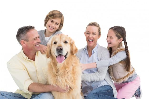 Retrato de familia sonriente sentado junto con su perro