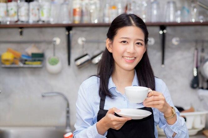 Retrato de hermosa joven barista bebiendo una taza de café.
