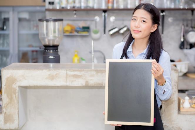 Retrato de hermosa joven barista, mujer asiática es un empleado de pie con pizarra