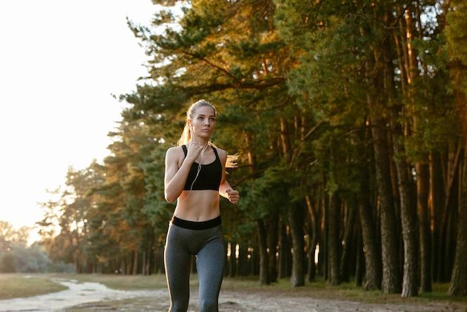 Retrato de hermosa mujer activa en auriculares para correr en la madera, escuchando música.