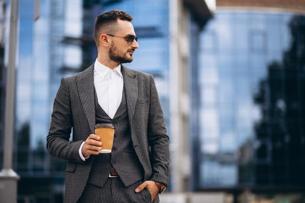 Retrato de hombre de negocios por el rascacielos tomando café
