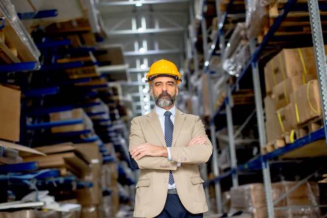 Retrato de hombre de negocios senior guapo en traje con casco en un almacén