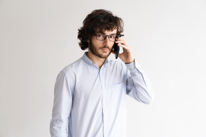 Retrato de hombre joven serio en gafas hablando por teléfono móvil.