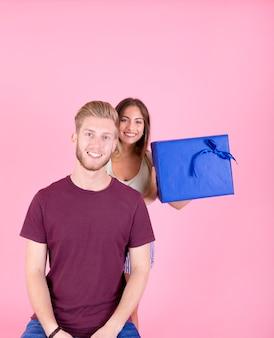 Retrato de hombre sonriente con su novia detrás de la celebración de caja de regalo azul