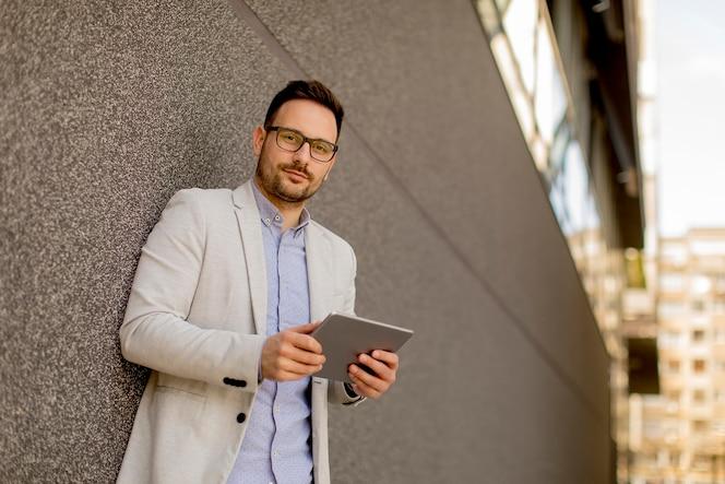 Retrato de joven empresario con pie de tableta digital al aire libre
