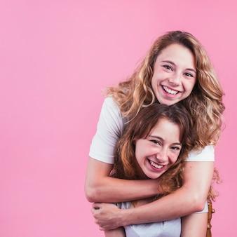 Retrato de joven mujer abrazando a su amiga sobre fondo rosa