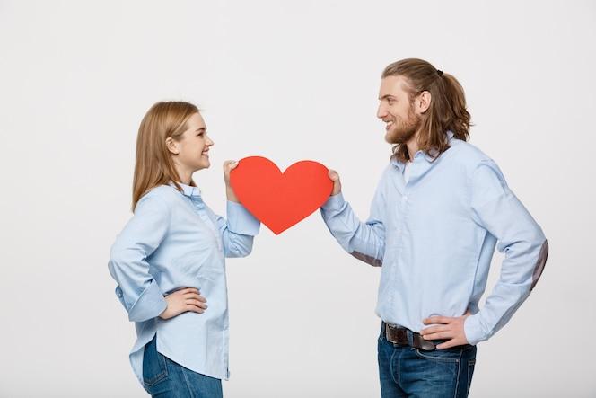 Retrato de joven pareja feliz en el amor con corazón de papel rojo