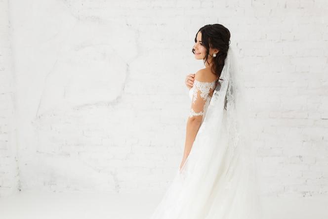 Retrato de la belleza de la novia con vestido de novia de moda con plumas