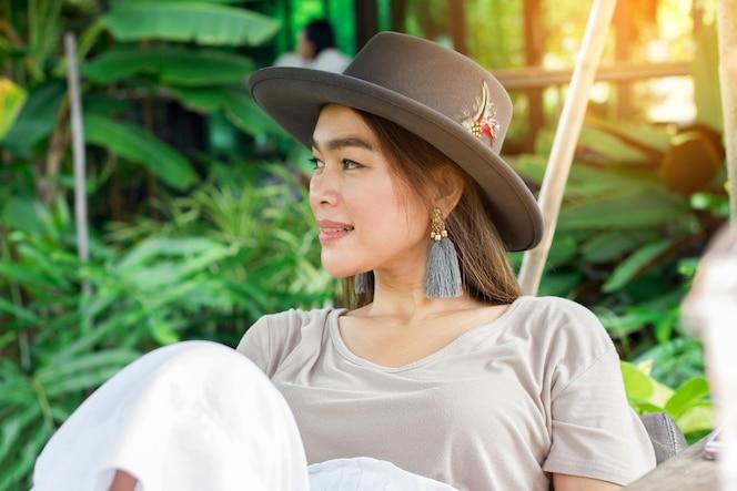 Retrato de la cabaña turística asiática del desgaste de la mujer que mira y que se relaja en la granja orgánica.