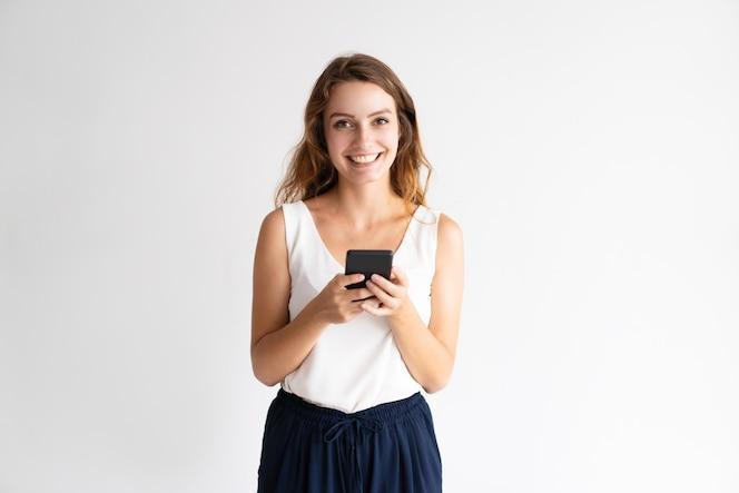 14b9cdd1d69bc Retrato de la mujer joven alegre que se coloca y que usa el teléfono móvil.