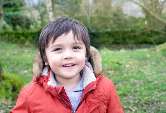 Retrato de lindo niño parado solo en el parque con cara sonriente