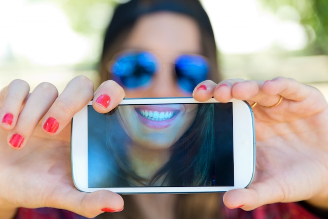 Retrato de muchacha hermosa que toma un selfie con el teléfono móvil en