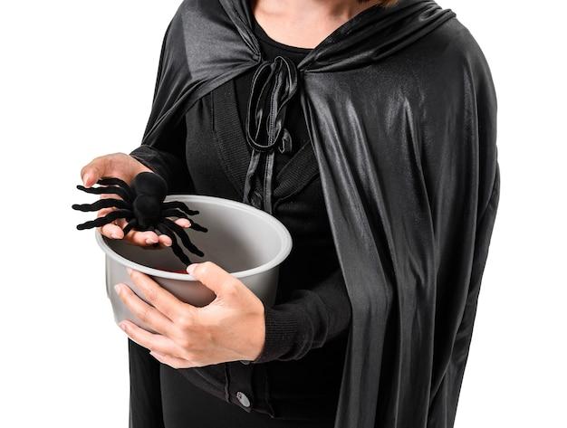 Retrato de mujer de negro scary bruja traje de halloween de pie con sombrero blanco aislado