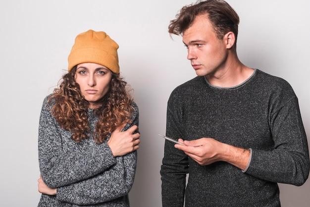 Retrato de pareja enferma con termómetro y pastillas con agua