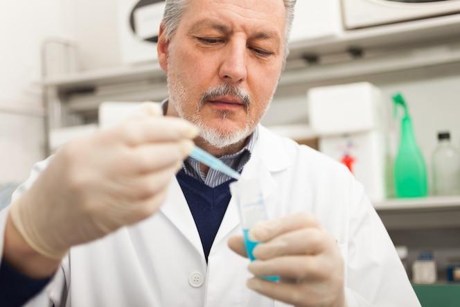 Retrato de primer plano de un investigador masculino con matraz con líquido azul en el laboratorio