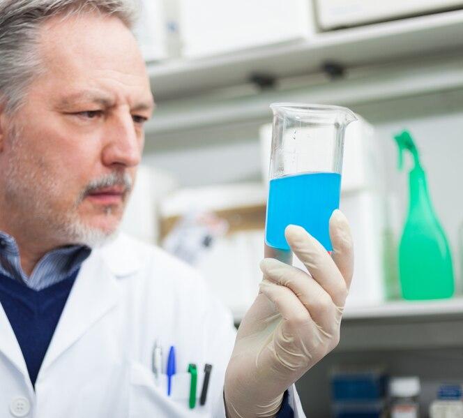 Retrato de primer plano de un investigador masculino sosteniendo un tubo de ensayo con líquido en el laboratorio