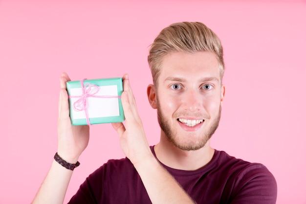 Retrato de sonriente joven sosteniendo una pequeña caja de regalo