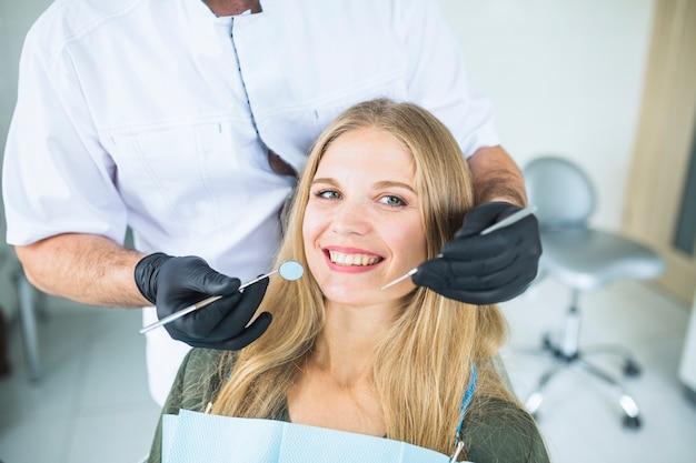 Retrato de sonriente paciente femenino durante el chequeo oral