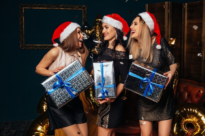 Retrato de tres mujeres jovenes sonrientes en el sombrero de papá noel con el regalo en manos.