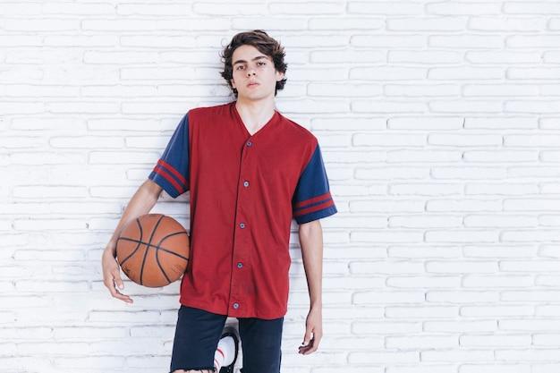 Retrato de un adolescente con baloncesto apoyado en la pared de ladrillo