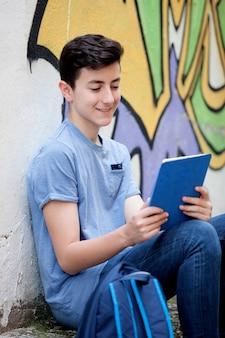 Retrato de un chico adolescente con una tableta en la calle