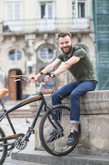Retrato de un feliz joven ciclista masculino con bicicleta