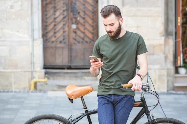 Retrato de un hombre con bicicleta de pie en el teléfono móvil