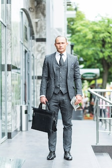 Retrato de un hombre de negocios con bolsa de ordenador portátil y periódico