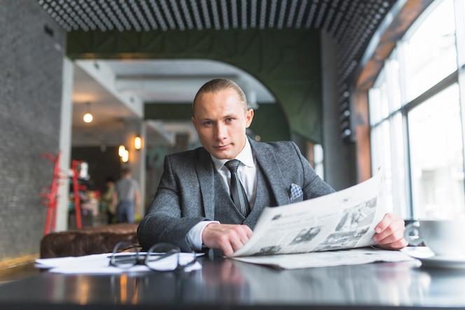 Retrato de un hombre de negocios con periódico sentado en la cafetería