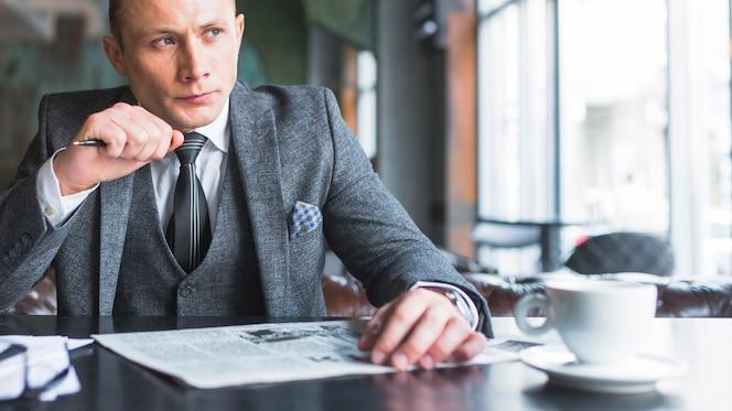 Retrato de un hombre de negocios serio con periódico mirando a otro lado