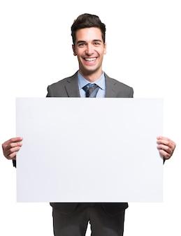 Retrato de un hombre de negocios sonriente sosteniendo un tablero blanco