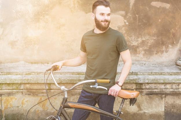 Retrato de un hombre joven con bicicleta mirando a otro lado