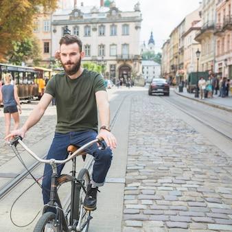 Retrato de un hombre joven que monta la bicicleta en la ciudad