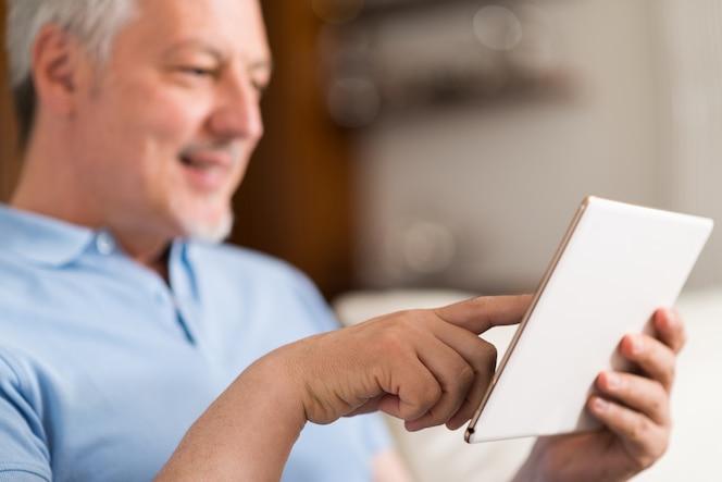 Retrato de un hombre senior sonriente con una tableta digital en la sala de estar de su casa