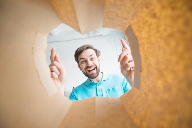 Retrato de un hombre sonriente mirando dentro de la bolsa de papel