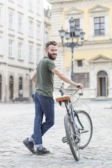 Retrato de un joven ciclista masculino con su bicicleta
