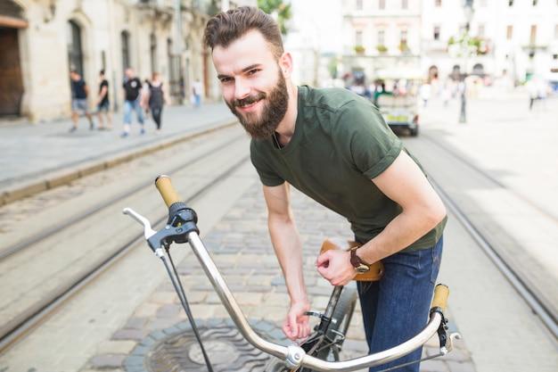 Retrato de un joven feliz ajuste de asiento de bicicleta
