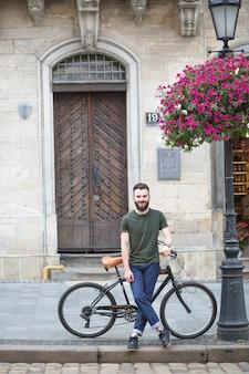 Retrato de un joven sonriente con bicicleta de pie sobre el pavimento