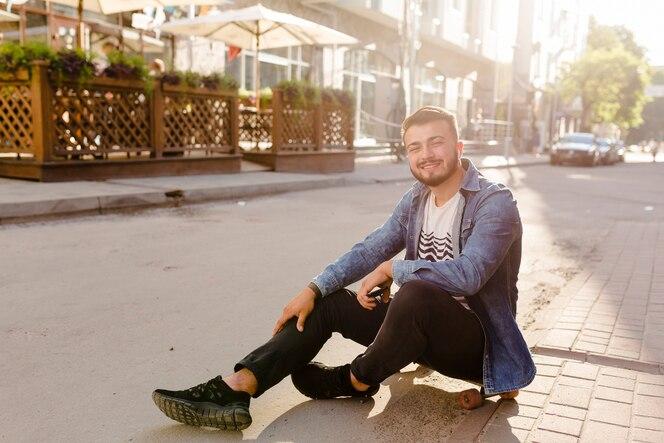 Retrato de un skater masculino joven que mira la cámara