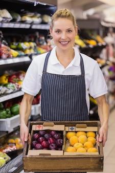 Retrato de un trabajador rubio sonriente sosteniendo una caja con verduras en el supermercado