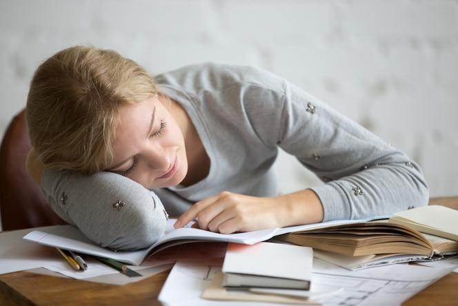 Retrato de una chica estudiante durmiendo en el escritorio